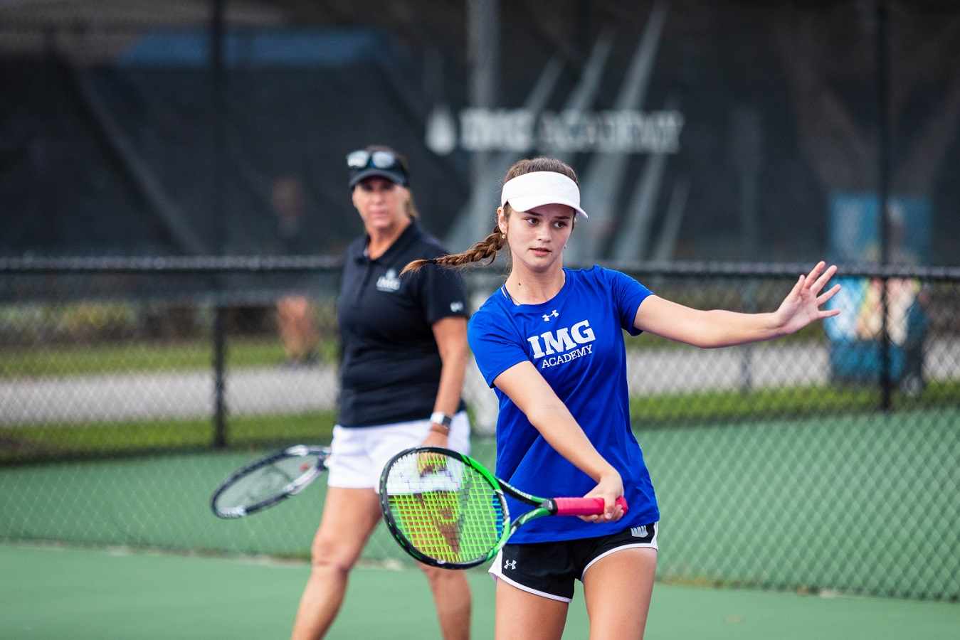 Female tennis player hits a shot while a coach looks on | IMGAcademy.com