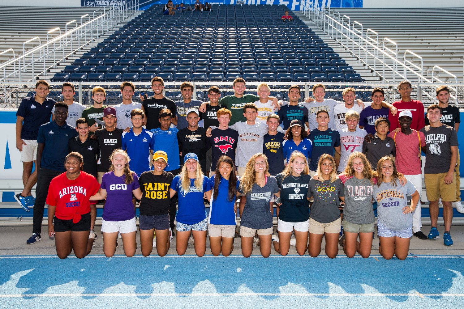 img academy student athletes pose wearing their college shirts at a spring commitment ceremony | IMGAcademy.com