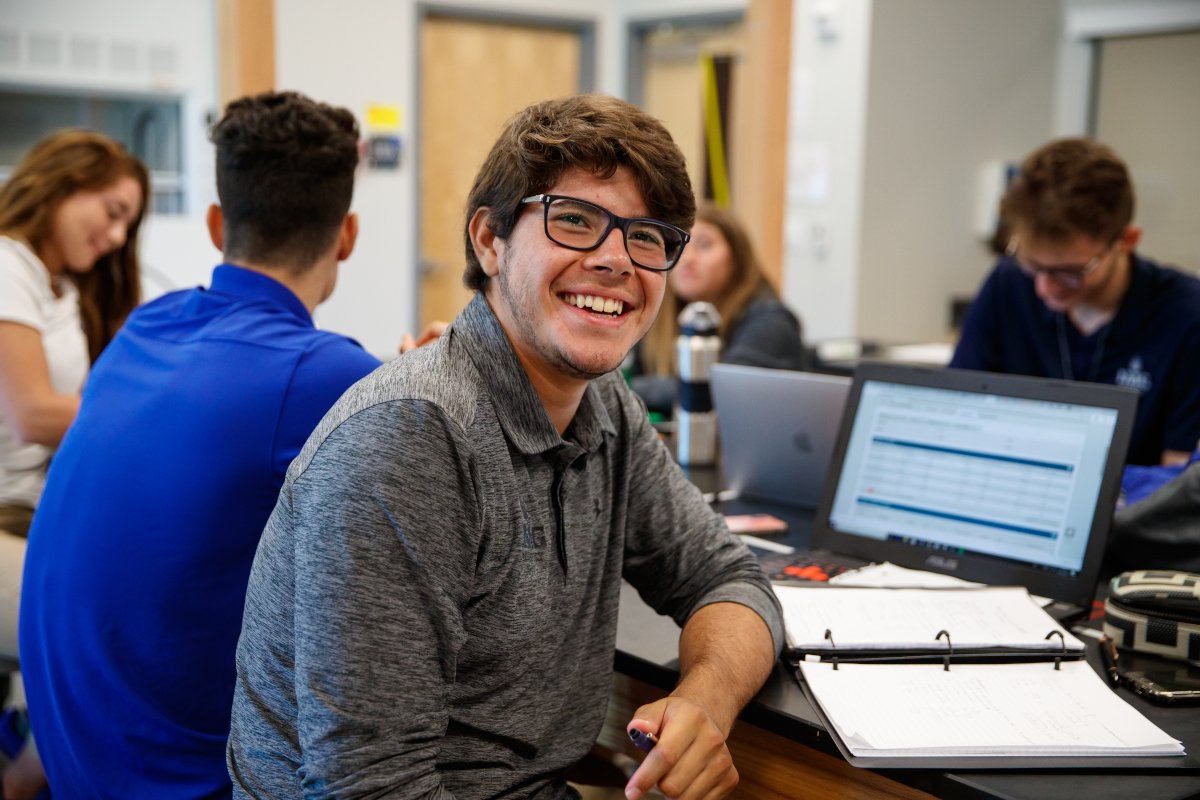 Smiling Male IMG Academy Student-Athlete Sitting in Class Next to His Notebook and Laptop with Classmates in the Background