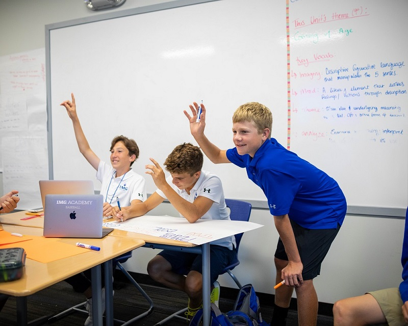 Three Male Students Raise Their Hands in Class | IMGAcademy.com