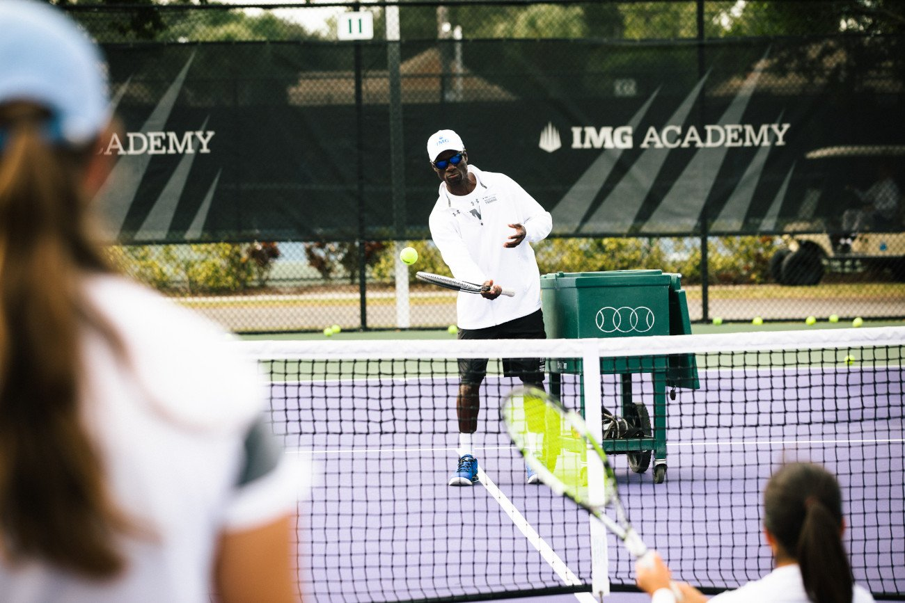 tennis coach works with players at IMG Academy | IMGAcademy.com