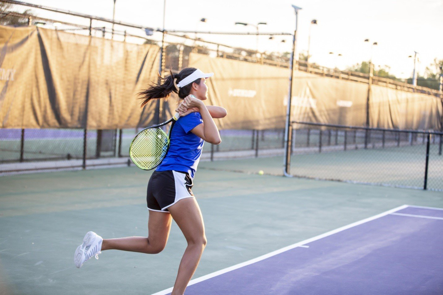 Female IMG Academy Junior Tennis Athlete Taking a Backhand Swing as She Runs Across the Court