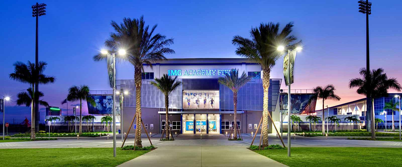 Sunset view of the IMG Academy stadium entrance surrounded by palm trees